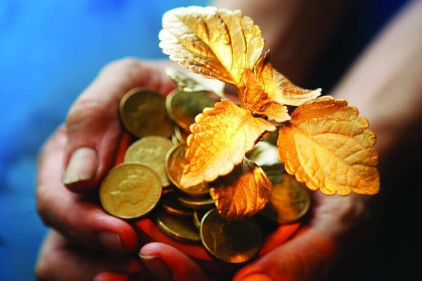 gold leaf and coins in hands investing outside superannuation