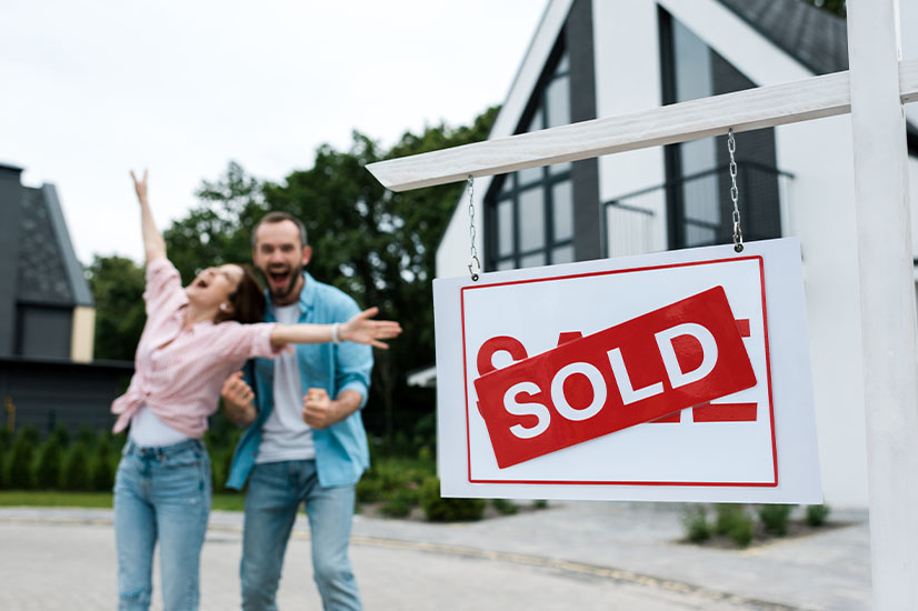 Couple near the sold sign of property