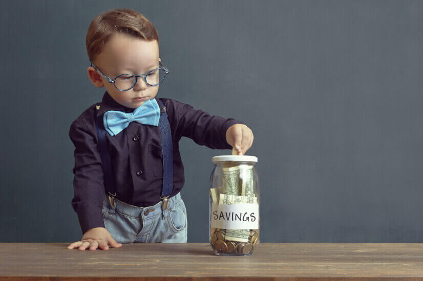 kid putting money in savings jar childs play kids savings account worth your time