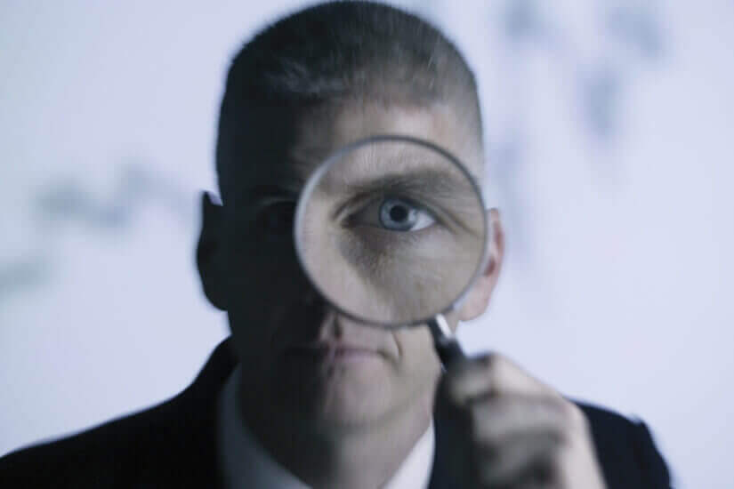 Investors watch, magnifying glass