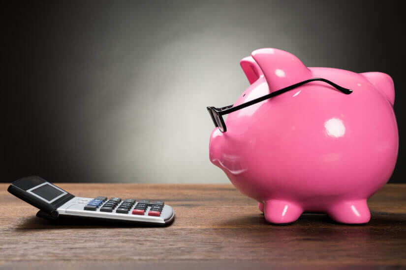 pink piggy bank looking at calculator superannuation transferring super fund to fund