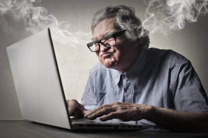 old senior man typing in laptop fuming mad steaming access to age pension unfair nightmare