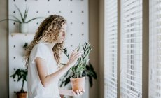 Girl holding a plant at home
