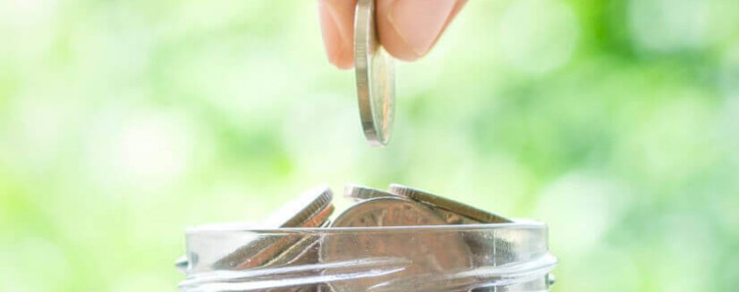 hands placing coins in a container borrow money from super fund