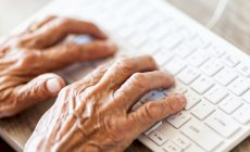 Elderly hands typing on a keyboard