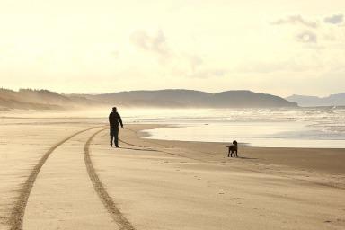 Old man walking down a beach